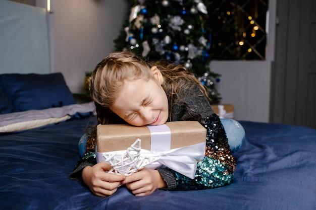 Klein schattig meisje kreeg een vakantiegift. geniet van het ontvangen van cadeautjes. kind opgewonden over het uitpakken van haar cadeau. kerstmis, vakantie en jeugdconcept
