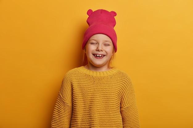 Klein schattig meisje lacht vrolijk, voelt zich blij nieuwe speelgoedpop van ouders te ontvangen, sluit de ogen, heeft plezier binnenshuis, draagt hoed met oren en losse gebreide trui, geïsoleerd over gele muur.