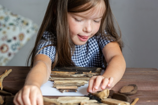 Klein schattig meisje maakt een kerstboomambacht van stokjescreativiteit van ecovriendelijke en natuurlijke materialen