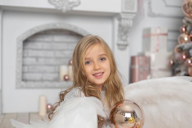 Klein schattig meisje met blond haar met engelenvleugels in de studio naast de kerstboom