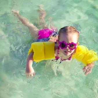 Klein schattig meisje met duiken in de zee in mooie zonnebril