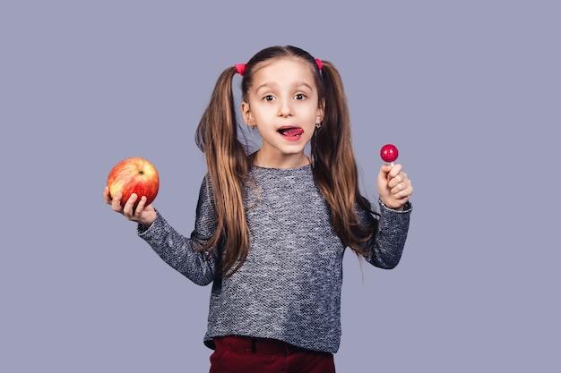 Klein schattig meisje met een snoepje en een appel in haar handen. conceptkeuze tussen gezond en ongezonde kost. geïsoleerd op grijze achtergrond