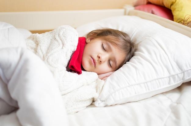 Klein schattig meisje met koude slaap onder deken