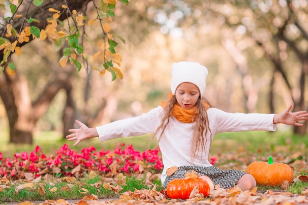 Klein schattig meisje met pompoen buiten op een warme herfstdag.