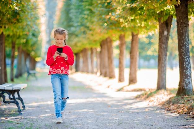 Klein schattig meisje met smartphone in de herfst. jong geitje dat pret heeft bij warme zonnige de herfstdag in openlucht