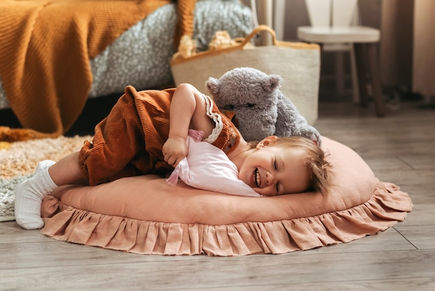 Klein schattig meisje peuterpret speelt met kussens in de kinderkamer