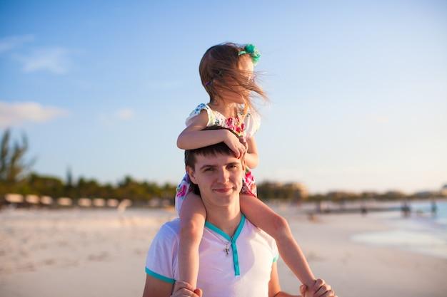 Klein schattig meisje rijden op haar vader wandelen langs het strand
