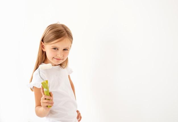 Klein schattig meisje schildert een muur met verfroller
