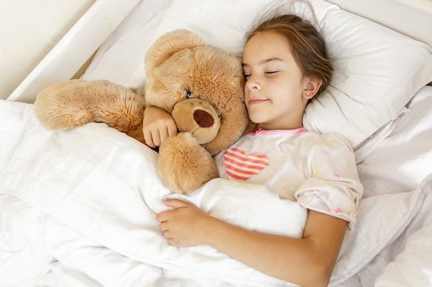 Klein schattig meisje slaapt en knuffelt grote teddybeer op bed