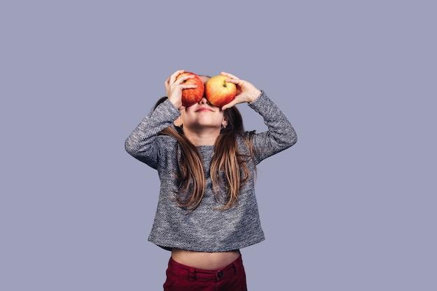 Klein schattig meisje sluit haar ogen met twee appels. geïsoleerd op grijs oppervlak