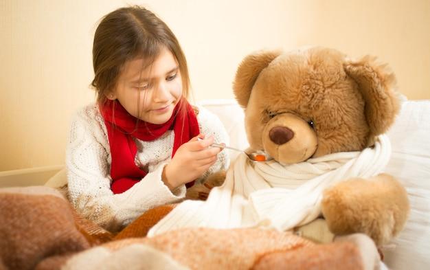 Klein schattig meisje speelt in het ziekenhuis met teddybeer