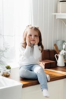 Klein schattig meisje spelen in de keuken, geluk, familie. koken.