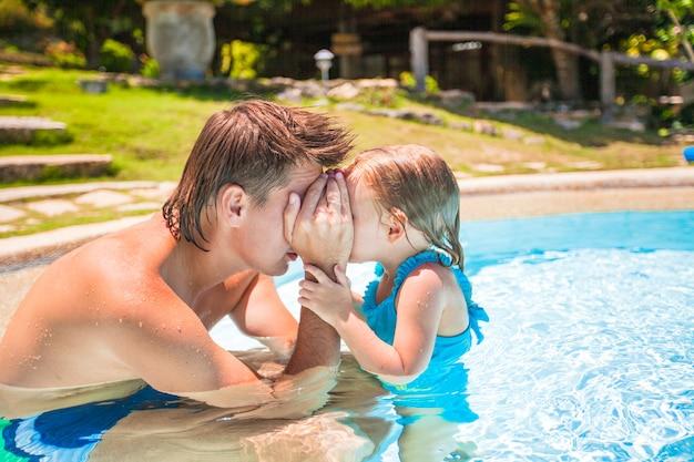 Klein schattig meisje spelen met vader bij het zwembad in tropisch hotel