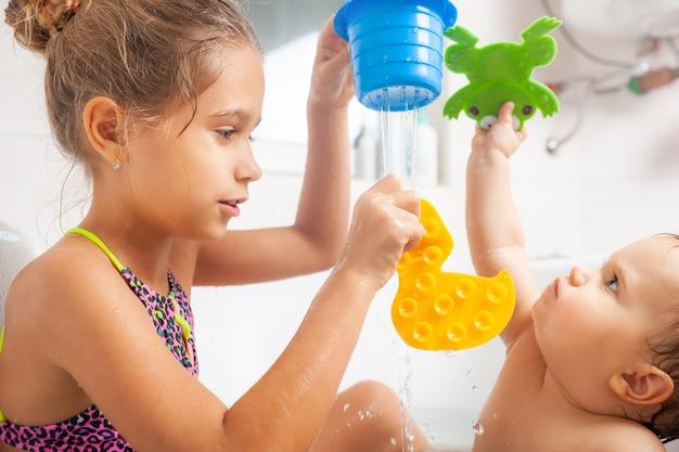 Klein schattig meisje toont haar kleine broertje een gele eend terwijl ze in een badkuip met water zit