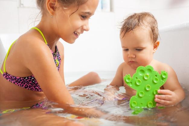 Klein schattig meisje toont haar kleine broertje een groene kikker zittend in een badkuip