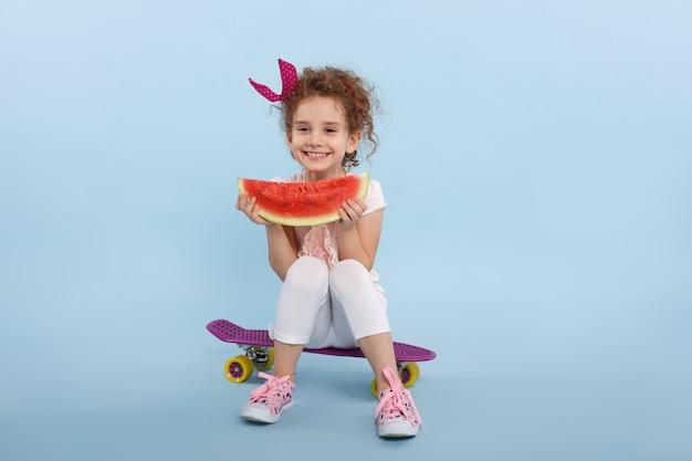 Klein schattig meisje watermeloen eten op een skateboard