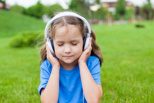 Klein schattig meisje zit in een park luisteren naar muziek in witte koptelefoon