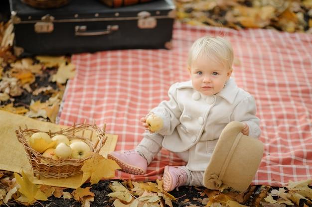 Klein schattig meisje zit op een plaid, eet een appel en houdt een hoed. herfst fotoshoot
