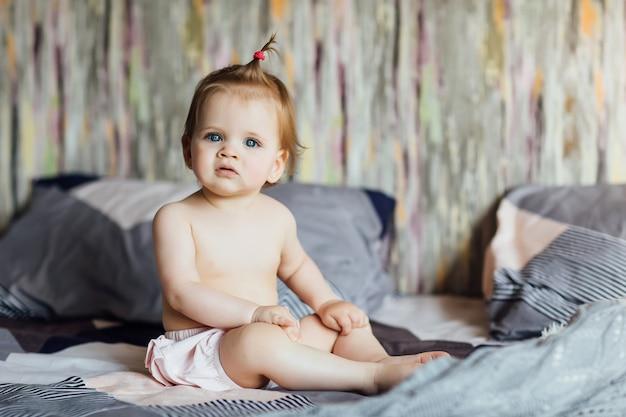 Klein schattig meisje zit op het bed met een mooi kapsel in de slaapkamer. thuis en levensstijl.