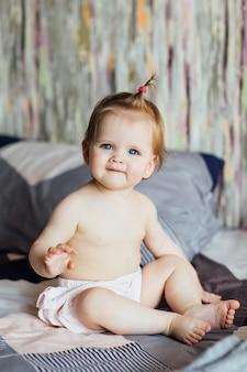 Klein schattig meisje zit op het bed met mooi kapsel in de slaapkamer