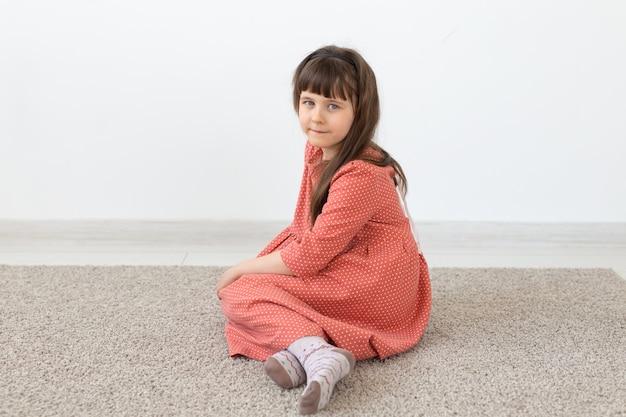 Klein schattig meisje, zittend met een bescheiden lange roze jurk tegen een witte muur. het concept van kleine onschuldige kinderen. advertentie ruimte