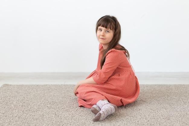 Klein schattig meisje, zittend met een bescheiden lange roze jurk tegen een witte muur