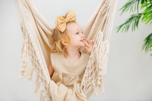 Klein schattig mooi kind meisje met een strik op haar hoofd swingend in een hangmat thuis