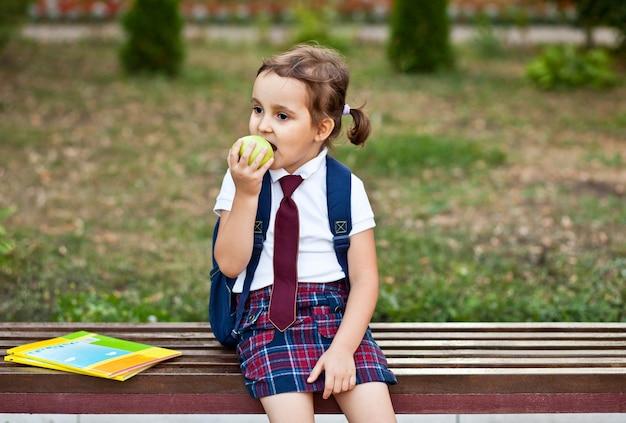 Klein schattig schoolmeisje in uniform zittend op een bankje en een appel etend