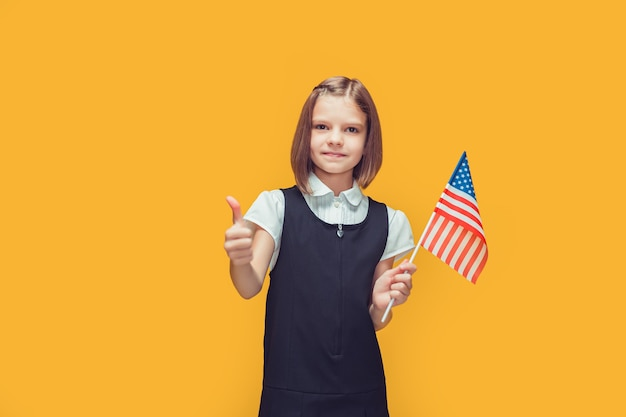Klein schattig schoolmeisje met amerikaanse vlag toont duim op gele achtergrond zoals amerika