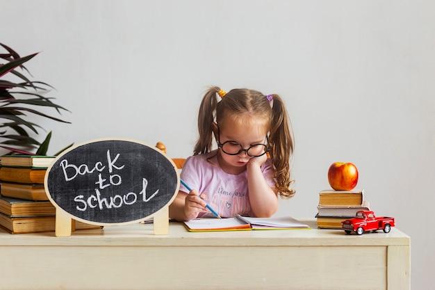 Klein schattig schoolmeisje met bril zit aan haar bureau op school met schoolboeken