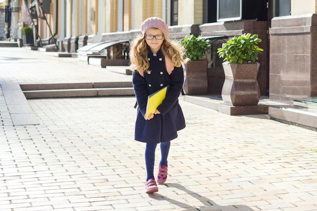 Klein schattig schoolmeisje met notitieboekjes