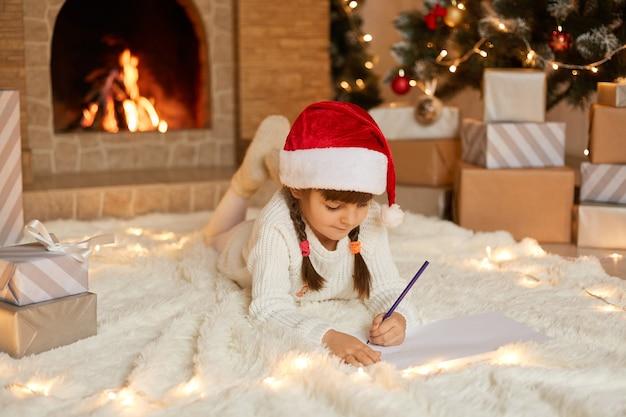 Klein schattig vrouwelijk kind liggend op de vloer op tapijt en schrijven brief aan de kerstman