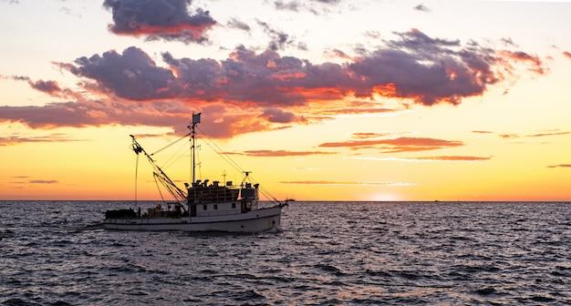 Klein schip in zee. zomerdag zonsondergang.