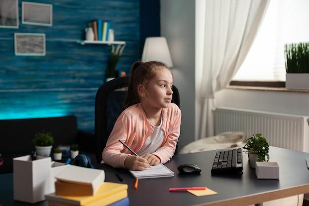 Klein scholier zit aan bureau tafel in woonkamer wiskunde huiswerk te maken