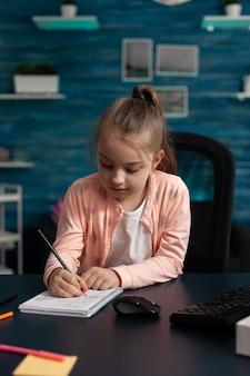 Klein scholiertje zit aan bureautafel in de woonkamer en schrijft wiskundeoefeningen