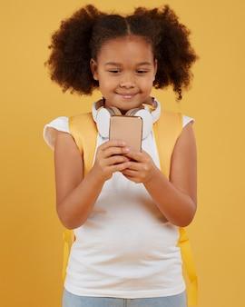 Klein schoolmeisje dat mobiele telefoon met behulp van