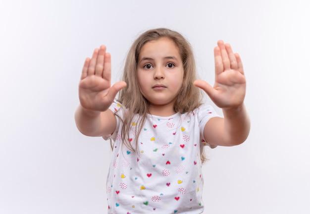 Klein schoolmeisje dat wit t-shirt draagt dat stopgebaar op geïsoleerde witte muur toont