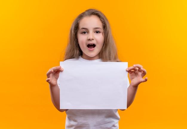 Klein schoolmeisje die wit t-shirt dragen die document op geïsoleerde oranje muur houden