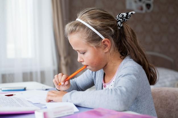 Klein schoolmeisje huiswerk maken