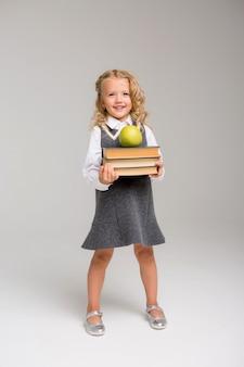 Klein schoolmeisje met boeken op een lichte achtergrond