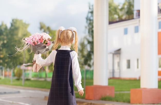Klein schoolmeisje met boeket gaat op zonnige dag naar school
