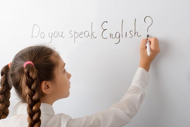 Klein schoolmeisje schrijven spreek je engelse inscriptie op het bord?