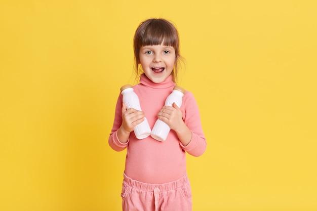 Klein schoonheidsmeisje die in roze kleren met bruin haar twee flessen melk op geel houden