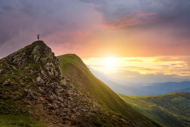 Klein silhouet van wandelaar die met opgeheven armen op de rotsachtige bergtop staat bij zonsondergang.