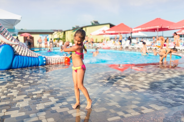 Klein slank schattig meisje in heldere zwembroek poseert op de achtergrond van de waterzone voor kinderen in een open lucht op warme zomerdag tijdens vakantie. concept van kinderanimatie en buitenactiviteiten.