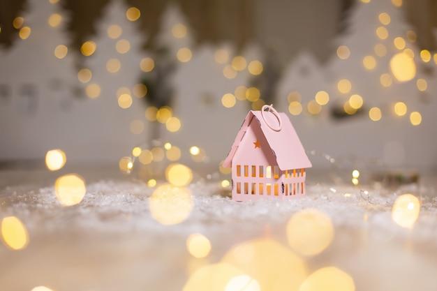Klein speelgoedhuisje, kerstverhaal feestelijk decor, warme bokehlichten.