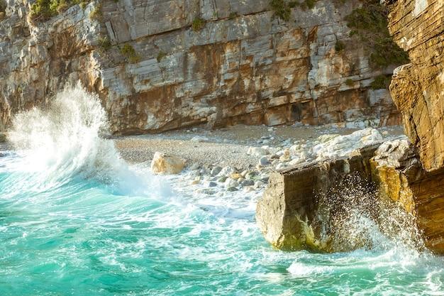 Klein strand aan een rotsachtige kust. zomeravond en zeesurfspray