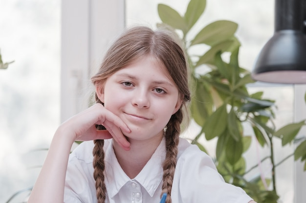 Klein studentenmeisje dat op school studeert. huishobby. glimlachend kindmeisje dat thuis schildert. laat je onderwijzen door de leraar versus leer en studeer thuis met de ouders. jong meisje huiswerk.