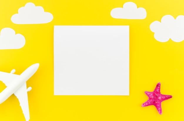 Klein stuk speelgoed vliegtuig met wolken en leeg document