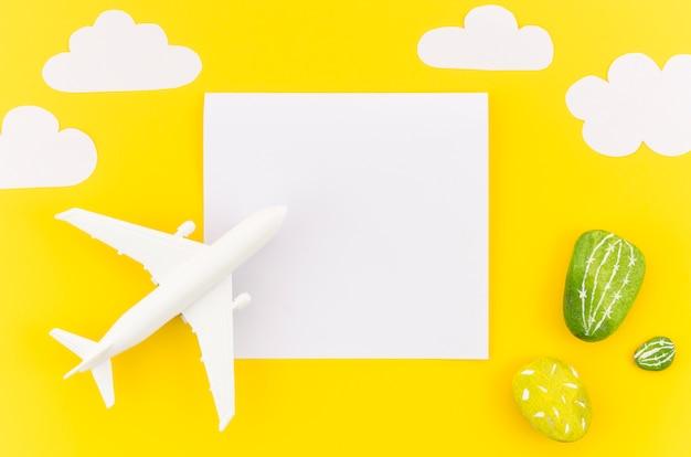 Klein stuk speelgoed vliegtuig met wolken en papier